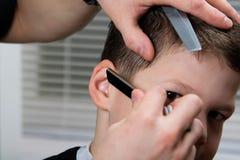 O cabeleireiro equilibra o penteado dos meninos Imagens de Stock