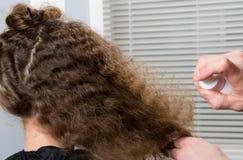 O cabeleireiro espirra no cabelo do ` s da criança, um remédio com as vitaminas para o penteado fácil fotos de stock