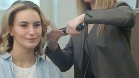 O cabeleireiro está fazendo o penteado, ondas de costas do cabelo pelo ferro de ondulação para uma mulher de sorriso que senta-se Foto de Stock Royalty Free