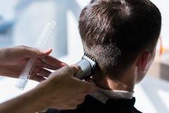 O cabeleireiro está nivelando um corte de cabelo com a ajuda de uma lâmina elétrica e de um pente em um close-up do barbeiro foto de stock royalty free