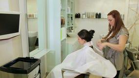 O cabeleireiro fêmea põe sobre o colar do cabeleireiro sobre o pescoço da menina antes do corte vídeos de arquivo