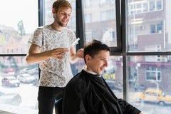 O cabeleireiro faz o cabelo com o pente do cliente satisfeito considerável no salão de beleza profissional do cabeleireiro imagens de stock royalty free