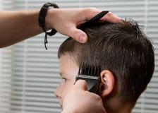 O cabeleireiro faz o cabelo para a criança, as tosquiadeiras Imagens de Stock Royalty Free
