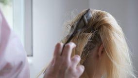 O cabeleireiro faz a coloração de cabelo no estúdio da beleza, a coloração profissional e os cuidados capilares, negócio da belez filme