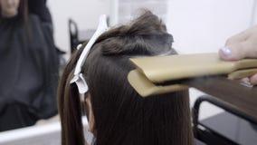 O cabeleireiro faz a laminação do cabelo em um salão de beleza para uma menina com cabelo moreno video estoque