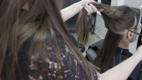 O cabeleireiro faz a laminação e o cabelo que endireitam em um salão de beleza para uma menina com cabelo marrom Conceito dos cui filme