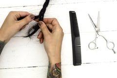 O cabeleireiro faz o penteado no worktop branco Imagem de Stock