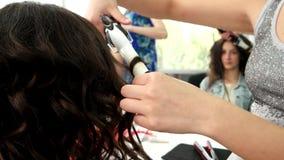 O cabeleireiro faz a ondas os tenazes de brasa do cabelo, ondulando para o cabelo, cabeleireiro do salão de beleza que trabalha c vídeos de arquivo