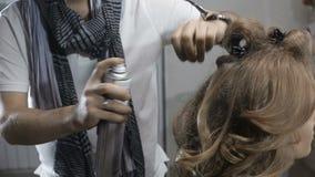 O cabeleireiro faz o penteado na menina na barbearia, pôs um verniz video estoque
