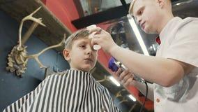 O cabeleireiro faz um corte de cabelo à moda para um rapaz pequeno no barbeiro Barbeiro que faz o cabelo do corte com ajustador d vídeos de arquivo