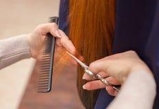 O cabeleireiro faz um corte de cabelo com as tesouras do cabelo Imagens de Stock