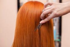 O cabeleireiro faz um corte de cabelo com as tesouras do cabelo a um jovem com a menina vermelha do cabelo Fotos de Stock