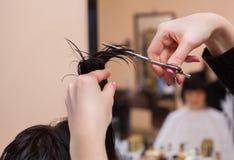 O cabeleireiro faz um corte de cabelo com as tesouras do cabelo a uma moça Fotografia de Stock Royalty Free