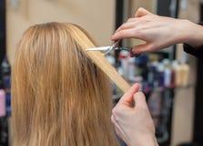 O cabeleireiro faz um corte de cabelo com as tesouras do cabelo a uma moça, um louro Imagens de Stock
