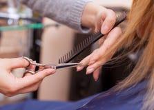 O cabeleireiro faz um corte de cabelo com as tesouras do cabelo a uma moça, um louro Fotografia de Stock Royalty Free