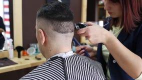 O cabeleireiro faz um penteado à moda para um cliente masculino vídeos de arquivo