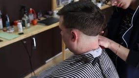O cabeleireiro faz um penteado à moda para um cliente masculino filme