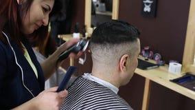 O cabeleireiro faz um penteado à moda para um cliente masculino video estoque