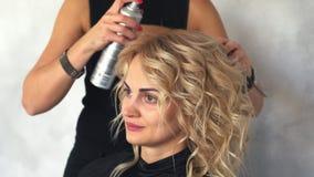 O cabeleireiro fixa ondas da laca no salão de beleza video estoque