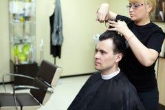 O cabeleireiro fêmea corta o cabelo do homem Foto de Stock Royalty Free