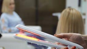O cabeleireiro guarda o ferro cozinhando quente do cabelo video estoque
