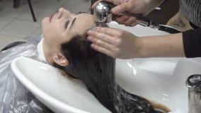 O cabeleireiro lava a pintura marrom do cabelo da menina na barbearia após o corte e a coloração de cabelo vídeos de arquivo