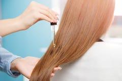 O cabeleireiro mestre aplica o óleo aos cuidados capilares para e restaura o crescimento da mulher das cutículas foto de stock royalty free