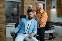O cabeleireiro mestre faz o penteado e o estilo com tesouras e pente Retrato da barba ? moda do homem Cabeleireiro e imagens de stock royalty free