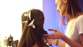 O cabeleireiro novo faz o penteado com mulher bonita video estoque