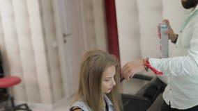 O cabeleireiro profissional adiciona a laca do cabelo no cabelo modelo Penteado do volume video estoque