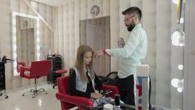O cabeleireiro profissional adiciona a laca do cabelo no cabelo modelo Penteado do volume vídeos de arquivo