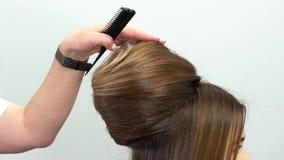 O cabeleireiro profissional demonstra o penteado terminado e termina alterações video estoque