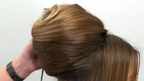 O cabeleireiro profissional demonstra o penteado terminado e termina alterações vídeos de arquivo