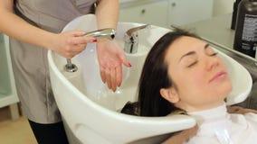 O cabeleireiro profissional do close-up lava o cliente da mulher do cabelo em um salão de beleza vídeos de arquivo
