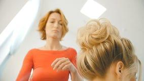 O cabeleireiro profissional, estilista que faz o penteado para a mulher bonita nova e que usa o pulverizador de cabelo no branco  filme