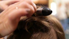 O cabeleireiro profissional faz a menina, penteado dos clientes filme