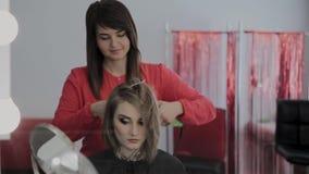 O cabeleireiro profissional faz o penteado de uma menina para uma sessão fotográfica video estoque