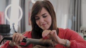 O cabeleireiro profissional faz o penteado de uma menina para uma sess?o fotogr?fica video estoque