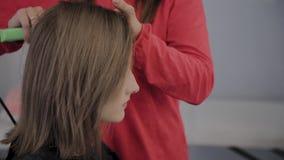 O cabeleireiro profissional faz o penteado de uma menina para uma sess?o fotogr?fica vídeos de arquivo