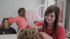 O cabeleireiro profissional faz o penteado de uma menina para uma sess?o fotogr?fica filme
