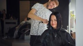 O cabeleireiro profissional masculino está endireitando o cabelo moreno do ` s da mulher usando um hairstraightener no cabeleirei vídeos de arquivo