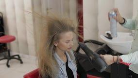 O cabeleireiro profissional que denomina sopros enverniza no cabelo modelo com um secador de cabelo filme