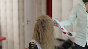 O cabeleireiro profissional que denomina sopros enverniza no cabelo modelo com um secador de cabelo video estoque