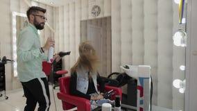 O cabeleireiro profissional que denomina sopros enverniza no cabelo modelo com um secador de cabelo vídeos de arquivo