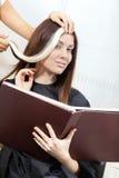 O cabeleireiro tenta o fechamento do cabelo tingido no cliente Fotos de Stock Royalty Free
