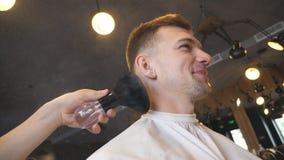 O cabeleireiro usa a escova ao cliente de limpeza do cabelo cutted no barbeiro Barbeiro masculino que usa um talco no pescoço do  video estoque