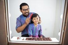 O cabelo da sua filha do pai escova imagens de stock royalty free