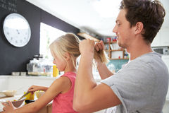 O cabelo de Styling Daughter do pai na tabela de café da manhã Foto de Stock