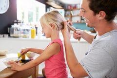 O cabelo de Styling Daughter do pai na tabela de café da manhã Imagem de Stock Royalty Free
