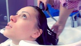 O cabelo do cliente da lavagem do barbeiro no salão de beleza no dissipador vídeos de arquivo